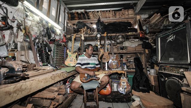 Potret Bone di sela aktivitasnya di workshop Bone's Costum Guitar, Jatinegara, Jakarta, Rabu (10/3/2021). Pandemi virus Corona menyebabkan usaha pembuatan dan servis gitar yang dirintis sejak 1989 itu nyaris tanpa pemasukan. (merdeka.com/Iqbal S Nugroho)