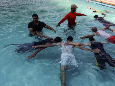 Anak muda Palestina yang diamputasi berlatih di bawah instruksi Majdi al-Tatar (kiri)  di kolam renang Kota Gaza (30/7/2019). Tatar, yang kehilangan kaki kanannya akibat kecelakaan pada masa kecilnya, melatih warga Palestina yang diamputasi selama konflik dengan Israel. (AFP Photo/Mahmud Hams)