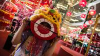 Seorang anak memakai topeng berbentuk barongsai saat mengunjungi Mall Taman Anggrek, Jakarta, Kamis (28/1/2021). Berbagai hiasan memeriahkan perayaan Tahun Baru Imlek 2572 mulai mewarnai pusat perbelanjaan di ibu kota. (Liputan6.com/Faizal Fanani)