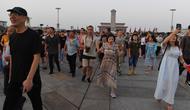 "Warga berjalan menghadiri upacara pengibaran bendera saat fajar setelah kematian mantan perdana menteri China Li Peng di Lapangan Tiananmen Beijing (24/7/2019). Li Peng biasa dikenal sebagai ""Jagal Beijing"" meninggal di usia 90 tahun. (AFP Photo/Greg Baker)"