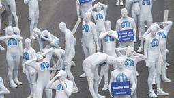 Aktivis dari Greenpeace mengenakan pakaian serba putih melakukan aksi teatrikal saat turun ke jalan di Stuttgart, Jerman (19/2). Mereka melakukan aksi memprotes polusi yang diakibatkan oleh knalpot mobil diesel. (Sebastian Gollnow/dpa/AFP)