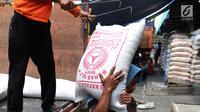 Seorang kuli angkut memanggul beras di Pasar Induk Cipinang, Jakarta, Senin (25/9). Penetapan HET beras kualitas medium zona Sumatera, NTT serta Kalimantan Rp 9.950 dan 13.300 per kilogram untuk kualitas premium. (Liputan6.com/Angga Yuniar)