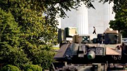 Seorang wanita berjalan ketika kendaraan pengangkut lapis baja Bradley terparkir di Lincoln Memorial, Washington, Rabu (3/7/2019). Presiden Donald Trump berencana memamerkan Tank-tank tempur sebagai bagian dari perayaan Hari Kemerdekaan AS yang dikenal sebagai Fourth of July. (AP/ Andrew Harnik)