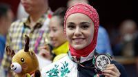 Atlet wushu Iran, Zahra Kiani menunjukkan medali perak dari nomor Qiangshu Asian Games 2018  di Jakarta, Selasa (21/8). (AP Photo/Aaron Favila)