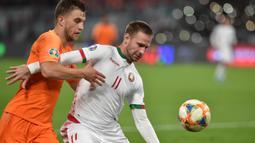 Bek Belanda, Joel Veltman, berebut bola dengan striker Belarusia, Maksim Skavysh, pada laga Kualifikasi Piala Eropa 2020 di Minsk, Minggu (13/10). Belarusia kalah 1-2 dari Belanda. (AFP/Sergei Gapon)