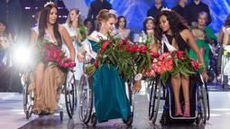 Miss Belarus Aleksandra Chichikova (tengah) terpilih sebagai Miss Wheelchair World di Warsawa, Polandia, Sabtu (7/10). Para kontestan berlaga dengan membawakan baju nasional, gaun cocktail dan gaun malam juga menampilkan tarian. (Wojtek Radwanski/AFP)
