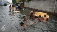 Sejumlah anak bermain di genangan air banjir di Kawasan Muara Angke, Jakarta, Rabu (11/1). Banjir ini juga telah merendam ratusan rumah, toko, dan tempat pengeringan ikan asin. (Liputan6.com/Gempur M. Surya)