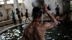 Pengunjung mengguyur kepala dengan air hangat dari belerang di Hamam Alli, Mosul, Irak, (27/4). Hammam Al Alil, yang berarti kamar Mandi Bagi Yang Sakit dalam bahasa Arab, kini opuler di kalangan pengungsi dan pasukan Irak. (AP Photo/Bram Janssen)