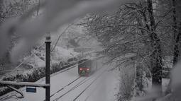 Sebuah kereta melaju di tengah salju di Milan, Italia (28/12/2020). Sekitar 20 sentimeter salju turun di kota itu, di mana seorang pria tunawisma berusia 76 tahun meninggal di rumah sakit setelah ditemukan di jalan. (Xinhua/Daniele Mascolo)