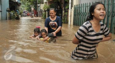 Warga melintasi banjir di kawasan Cipinang Melayu, Jakarta Timur, Senin (20/2). Banjir ini merendam RW 3 hingga RW 4, Kelurahan Cipinang Melayu, Kecamatan Cipinang Muara. (Liputan6.com/Yoppy Renato)