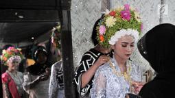 Gadis dirias oleh keluarga sebelum mengikuti Upacara Adat Ngarot di Desa Lelea, Kabupaten Indramayu, Jawa Barat, Rabu (19/12). Ngarot digelar sebagai bentuk rasa syukur menjelang musim tanam padi. (Merdeka.com/Iqbal Nugroho)