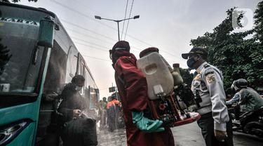 Petugas pemadam kebakaran wilayah Kecamatan Ciracas saat menyemprotkan disinfektan kepada penumpang bus AKAP yang baru tiba di Terminal Kampung Rambutan, Jakarta, Minggu (23/5/2021). (merdeka.com/Iqbal S Nugroho)