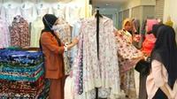 Emak-emak memilih mukenah raga motif yang dijual di pasar Pekanbaru. (Liputan6.com/M Syukur)