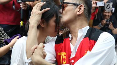 Terdakwa Tio Pakusadewo mencium anaknya Risa saat menjalani sidang putusan di PN Jakarta Selatan, Selasa (24/7). Majelis hakim memvonis Tio Pakusadewo dengan hukuman sembilan bulan masa tahanan dan enam bulan rehabilitasi. (Liputan6.com/Immanuel Antonius)