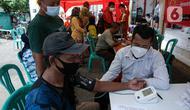 Petugas melakukan screening terhadap penerima vaksin COVID-19 di Pasar Gang Kancil, Jakarta Barat, Senin (2/8/2021). Gubernur Anies Baswedan mengatakan pemprov DKI telah memenuhi target Presiden Joko Widodo untuk menyalurkan vaksinasi dosis pertama kepada 7,5 juta orang. (Liputan6.com/Faizal Fanani)