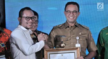 Gubernur DKI Jakarta Anies Baswedan (kanan) menerima penghargaan dari Menteri Ketenagakerjaan Hanif Dhakiri (kiri) dalam Indeks Pembangunan Ketenagakerjaan (INTEGRA) 2018 di Kantor Kemnaker, Jakarta, Senin (19/11). (Merdeka.com/Iqbal Nugroho)