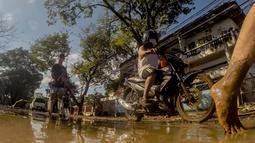 Warga berjalan di sebuah jalan yang tertutup lumpur akibat banjir yang dipicu Topan Vamco di Manila, Filipina (13/11/2020). Pemerintah Filipina pada Jumat (13/11) mengatakan Topan Vamco, yang memicu banjir besar dan tanah longsor menelan sedikitnya 14 korban jiwa. (Xinhua/Rouelle Umali)