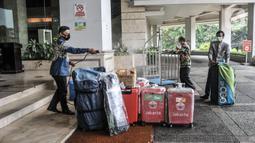 Petugas menyemprotkan cairan disinfektan pada barang-barang milik atlet kontingen DKI Jakarta saat tiba di Hotel Grand Cempaka Business, Jakarta, Kamis (14/10/2021). Nantinya para atlet ini akan menjalani tes swab PCR secara rutin tiap harinya serta tes malaria. (merdeka.com/Iqbal S. Nugroho)