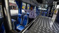 Petugas mengecek kondisi dalam bus Transjabodetabek Premium milik Perum PPD saat menunggu calon penumpang di Tamini Square, Jakarta, Kamis (14/12). (Liputan6.com/Faizal Fanani)