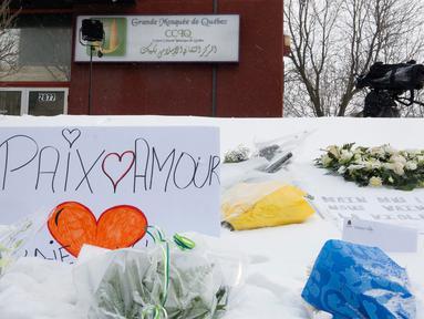 Sejumlah bunga berada di depan Masjid Quebec setelah penembakan brutal yang menewaskan jemaah masjid di Quebec, Kanada, (2/2). Akibatnya penembakan enam orang tewas dan 12 orang lain menderita luka ringan. (Jacques Boissinot/The Canadian Press via AP)
