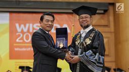 Rektor Universitas Terbuka Drs. Ojat Darojat, M.Bus., Ph.D memberikan cinderamata kepada Kepala Staf Kepresidenan Moeldoko usai memberikan orasi ilmiah saat wisuda Universitas Terbuka, Tangerang Selatan, Selasa (3/7). (Liputan6.com/Faizal Fanani)
