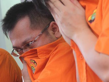 Tersangka menutupi wajahnya saat rilis kasus narkotika jenis sabu di Polda Metro Jaya, Jakarta, Rabu (16/1). Polisi menangkap empat orang tersangka, di mana salah satunya mengaku sebagai mantan kekasih penyanyi Syahrini. (Liputan6.com/Immanuel Antonius)