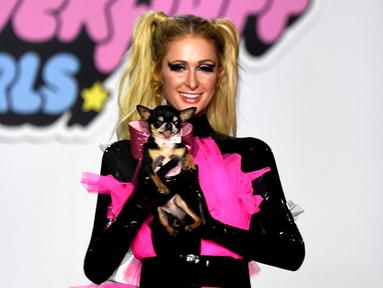 Paris Hilton membawa anjing saat tampil dalam Christian Cowan x The Powerpuff Girls Fashion Show, Los Angeles, AS, Jumat (8/3). Anjing tersebut merupakan peliharaannya yang bernama Diamond Baby. (Frazer Harrison/Getty Images North America/AFP)
