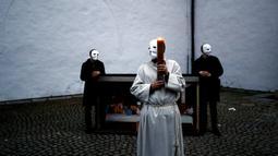 Para peserta yang mengenakan masker berdiri dekat lukisan Perjamuan Terakhir saat prosesi Paskah melawati jalan-jalan di Ceske Budejovice, Republik Ceko, Kamis (1/4/2021).Para peserta mengenakan masker dan menjaga jarak sosial sebagai tindakan pencegahan COVID-19.  (AP Photo/Petr David Josek)