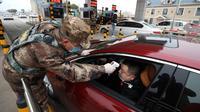 Anggota milisi mengukur suhu pengemudi mobil di sebuah pos pemeriksaan gerbang tol di Wuhan, Provinsi Hubei, China, Kamis (23/1/2020). Pemerintah China mengisolasi Kota Wuhan yang berpenduduk sekitar 11 juta jiwa untuk menahan penyebaran virus corona. (Chinatopix via AP)