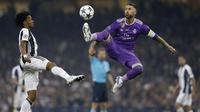 Kapten Real Madrid, Sergio Ramos, mengamankan bola dari gelandang Juventus, Juan Cuadrado, pada laga final Liga Champions di Stadion Stadion Millenium, Cardiff, Sabtu (3/6/2017). Madrid menang 4-1 atas Juventus. (AFP/Adrian Dennis)