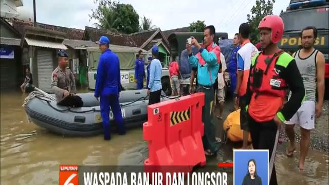 Dengan menggunakan perahu karet, petugas mendistribusikan bantuan kepada para korban di Desa Teluk dan Desa Kalanganyar.