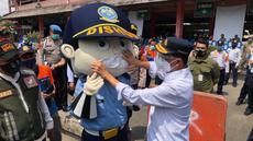 Menteri Perhubungan Budi Karya Sumadi memasangkan masker pada boneka Dishub di Terminal Kampung Rambutan, Jakarta, Kamis (29/10/2020). Budi Karya melakukan edukasi kepada penumpang yang masih banyak menggunakan masker scuba untuk memakai masker medicated atau berlapis. (Dok: Kemenhub)
