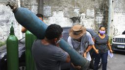 Anggota keluarga pasien COVID-19 yang dirawat di rumah sakit membawa tangki oksigen kosong untuk mengisinya kembali, di Manaus, negara bagian Amazonas, Brasil, 15 Januari 2021. Negara Bagian Amazonas di Brasil kehabisan oksigen karena semakin melonjaknya pasien Covid-19. (AP Photo/Edmar Barros)