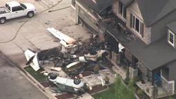Sebuah pesawat kecil yang sengaja menabrak rumah di Payson, Utah, AS, Senin (13/8). Pria bernama Duane Youd itu melakukan serangan yang mencengangkan hanya beberapa jam setelah ditangkap karena menyerang istrinya. (John Wilson/KSL-TV/Deseret News via AP)