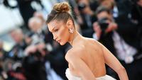 """Model AS Bella Hadid berpose ketika ia tiba menghadiri pemutaran film """"Rocketman"""" di Festival Film Cannes edisi ke-72 di Cannes, Prancis (16/5/2019). Bella Hadid tampil cantik mengenakan gaun tulle semi-tipis putih yang memukau oleh Dior Haute Couture. (AFP Photo/Loic Venance)"""