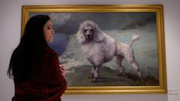 """Pekerja melihat lukisan """"Pudel"""" karya Maud Earl di museum anjing """"Museum of the Dog"""" di New York City, 1 Februari 2019. Museum of the Dog dibuka pada 8 Februari 2019 yang berisi berbagai koleksi seni bertema anjing terbesar di dunia. (Johannes EISELE/AFP)"""