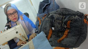 Perajin Risma Eljundi menyelesaikan pembuatan tas dari bahan celana jeans bekas di Legok, Tangerang, Banten, Senin (11/11/2019). Tas berbahan jeans itu dipasarkan ke kawasan Bandung serta pasar daring. (merdeka.com/Arie Basuki)