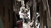 Warga setempat terlihat berupaya keluar dari dalam bangunan yang hancur akibat serangan udara yang dipimpin Arab Saudi di Sanaa, ibukota Yaman, 16 Mei 2019.(AFP)