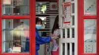 Seorang perempuan yang mengenakan masker membuka pintu toko optik di kota Quezon, Filipina, Selasa (22/9/2020). Presiden Filipina Rodrigo Duterte mengatakan telah memperpanjang status masa darurat virus corona (Covid-19) di negaranya hingga satu tahun ke depan. (AP Photo/Aaron Favila)