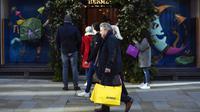 Orang-orang berjalan melewati toko sambil membawa tas belanja di Mayfair setelah pelonggaran pembatasan virus corona COVID-19 menyusul berakhirnya kebijakan penguncian nasional atau lockdown kedua di Inggris, di London, Sabtu (5/12/2020). (AP Photo/Alberto Pezzali)