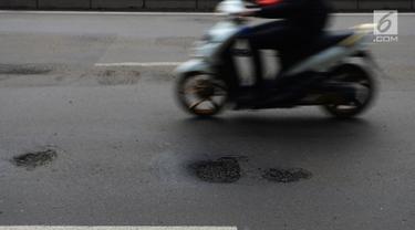 Pengendara motor melintas menghindari jalan berlubang di Jalan Gunung Sahari, Jakarta, Selasa (9/4). Meskipun sudah dilakukan penambalan, jalan raya tersebut sering rusak akibat beban kendaraan yang melintas di atasnya dan intensitas hujan yang belakangan ini cukup tinggi. (merdeka.com/Imam Buhori)