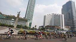 Pebalap sepeda melewati bundaran HI selama  even Tour de Jakarta 2016, Sabtu (30/7). Tour de Jakarta merupakan balapan di tengah kota dengan jarak tempuh 175,5 km yang terbagi dalam 13 putaran. (Liputan6.com/Immanuel Antonius)