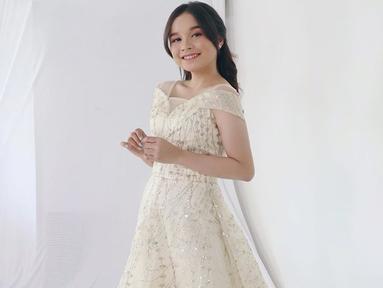 Dengan gaun putih, penampilan Tasya Rosmala nampak elegan dan menawan. Gadis 17 tahun ini selalu tampil fresh dan simple baik saat manggung atau dalam kegiatan sehari-harinya. (Liputan6.com/IG/@tasya_ratu_gopo)
