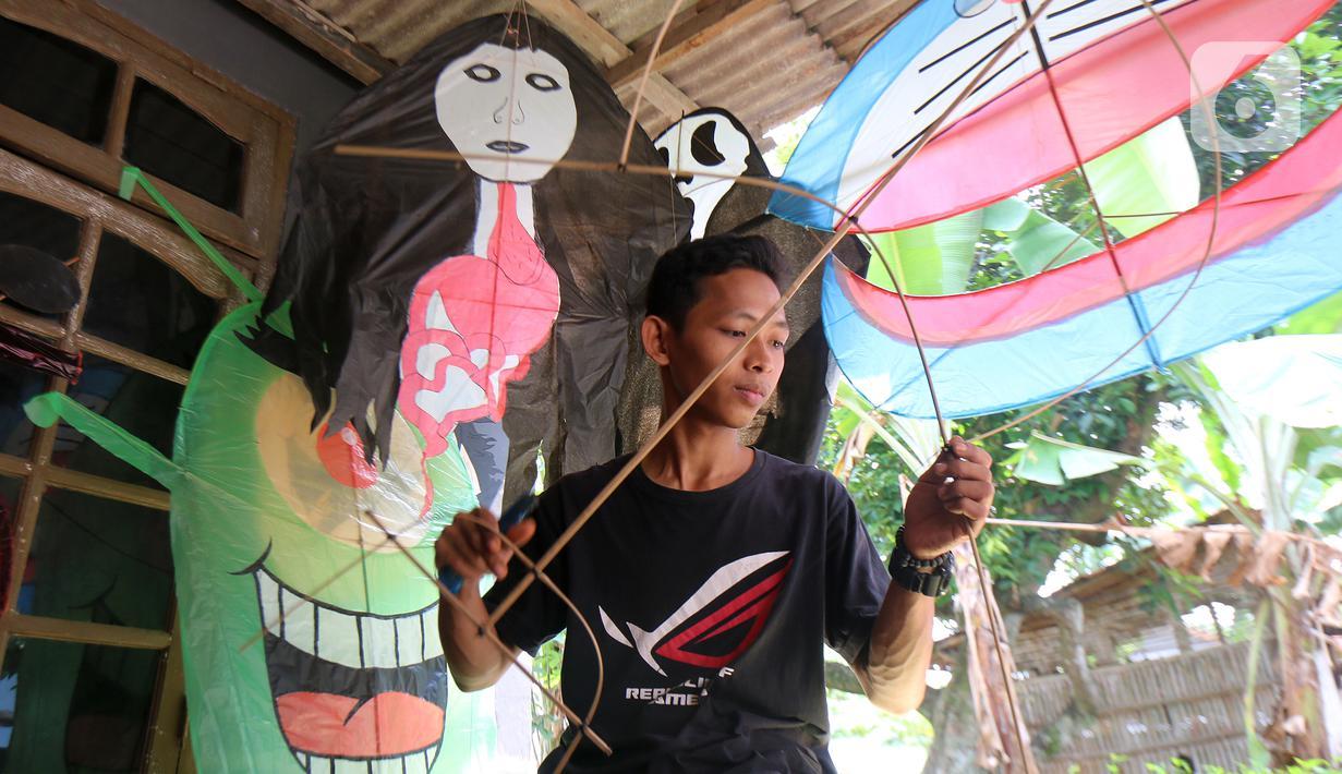 Perajin menyelesaikan pembuatan layang-layang Koang di Bedahan, Depok, Jawa Barat, Senin (20/7/2020). Kerajinan layangan berbahan rangka bambu, plastik, dan kain ramai diburu pada musim kemarau. (Liputan6.com/Fery Pradolo)