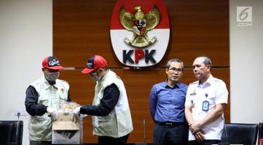 Dua petugas, Wakil Ketua KPK Alexander Marwata (kedua kanan) dan Irjen Kemenkum HAM Jhoni Ginting (kanan) jelang keterangan pers OTT di Gedung KPK, Jakarta (28/5/2019). OTT terkait penanganan perkara penyalahgunaan izin tinggal di Kantor Imigrasi Kelas I Mataram, NTB. (Liputan6.com/Johan Tallo)