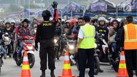 Polisi menahan sementara antrean pemudik bermotor yang akan masuk ke dalam kapal penyeberangan di Pelabuhan Merak, Banten, Jumat (23/6). H-2 Lebaran 2017, ribuan pemudik bermotor memadati dermaga 6 Pelabuhan Banten. (Liputan6.com/Helmi Fithriansyah)
