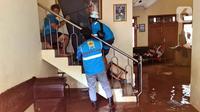 Petugas PLN membantu warga memindahkan lemari es saat memeriksa jaringan listrik yang sudah diputus agar tidak membahayakan, Bango, Pondok Labu, Jakarta, Sabtu (20/2/2021). Banjir di Jakarta berdampak pada pemadaman di sejumlah wilayah. (merdeka.com/Arie Basuki)