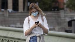"""Seorang wanita yang mengenakan masker berjalan di Jembatan Westminster di London, Inggris (8/9/2020). Warga Inggris didesak untuk menangani pandemi dengan serius atau menghadapi """"jalan bergelombang"""" di masa yang akan datang. (Xinhua/Han Yan)"""