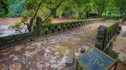 Banjir yang melanda Wilayah Dongxi di Distrik Qijiang, Kota Chongqing, China barat daya (1/7/2020). Guyuran hujan telah menyebabkan peningkatan debit air ke sungai-sungai di daerah pusat kota, dan beberapa pagar pengaman di sepanjang sungai rusak oleh derasnya arus air. (Xinhua/Chen Xingyu)