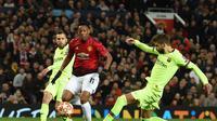 Gerard Pique menghentikan pergerakan Anthony Martial pada leg 1, babak perempat final Liga Champions yang berlangsung di Stadion Old Trafford, Manchester. Kamis (11/4). Barcelona menang 1-0 atas Man United. (AFP/Oli Scarff)